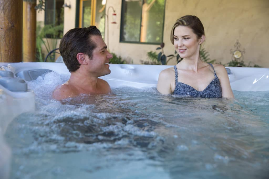 Man and woman soaking in a hot tub.