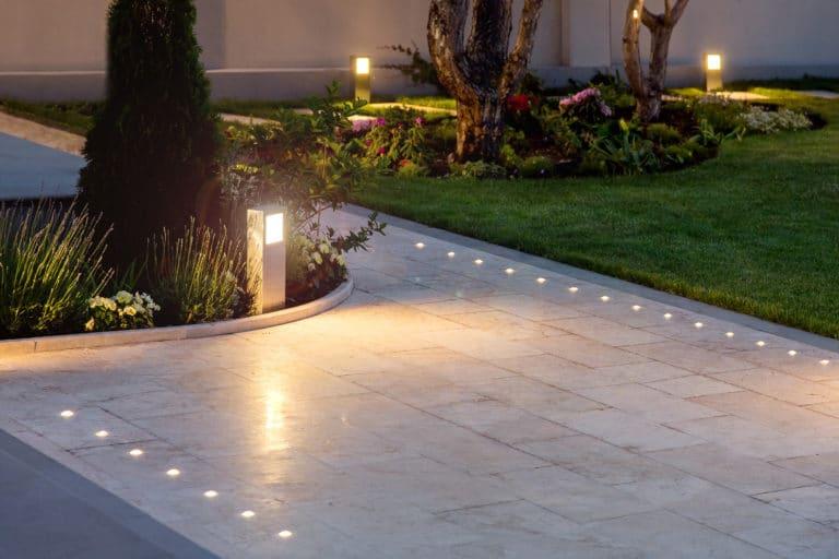 Modern backyard illuminated with in-ground lighting.